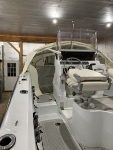 Triumph 210 center console fishing boat with bow dodger canvas tent